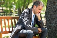 Depressed businessman sitting on park bench. Depressed businessman with hand on chin sitting on park bench Stock Photo