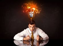 Businessman sitting under a blowing idea bulb Stock Images