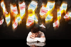 Depressed businessman sitting under burning tax and bill papers Stock Image