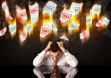 Depressed businessman sitting under burning tax and bill papers Royalty Free Stock Photography