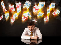 Depressed businessman sitting under burning tax and bill papers Royalty Free Stock Photo