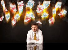 Depressed businessman sitting under burning tax and bill papers Stock Photography
