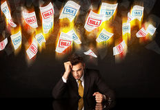 Depressed businessman sitting under burning tax and bill papers Stock Images