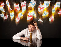 Depressed businessman sitting under burning tax and bill papers Royalty Free Stock Photos