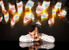 Depressed businessman sitting under burning tax and bill papers Royalty Free Stock Image