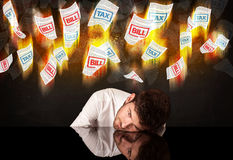 Depressed businessman sitting under burning tax and bill papers Royalty Free Stock Images