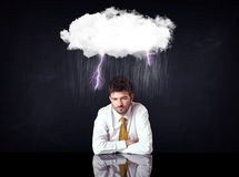 Depressed businessman sitting under a cloud Royalty Free Stock Image