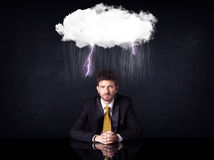 Depressed businessman sitting under a cloud Royalty Free Stock Photography