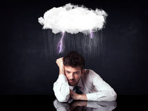 Depressed businessman sitting under a cloud Stock Photos