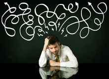 Depressed businessman sitting under drawn direction lines Royalty Free Stock Photography