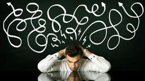 Depressed businessman sitting under drawn direction lines Stock Images