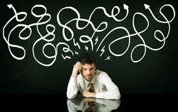 Depressed businessman sitting under drawn direction lines Stock Photos
