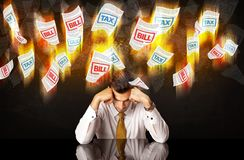 Depressed businessman sitting under burning tax and bill papers Stock Photo