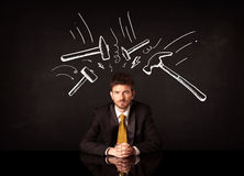 Depressed businessman sitting under hammer marks Stock Photo