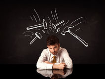 Depressed businessman sitting under hammer marks Stock Photos