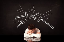 Depressed businessman sitting under hammer marks Stock Images