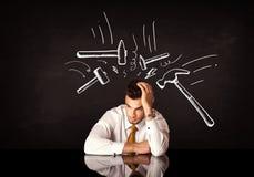 Depressed businessman sitting under hammer marks Stock Image