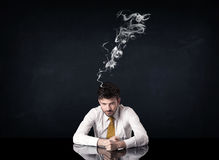 Depressed businessman with smoking head Stock Photo