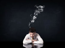 Depressed businessman with smoking head Royalty Free Stock Photography