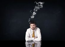 Depressed businessman with smoking head Stock Photography