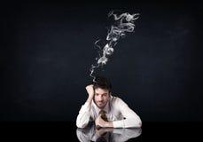 Depressed businessman with smoking head Stock Photo