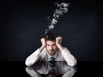 Depressed businessman with smoking head Royalty Free Stock Photos