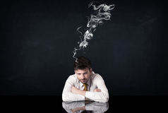 Depressed businessman with smoking head Stock Photos