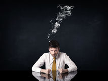 Depressed businessman with smoking head royalty free stock image
