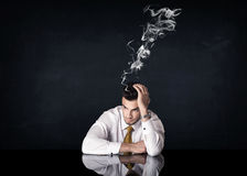 Depressed businessman with smoking head Royalty Free Stock Images