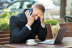 Depressed Businessman Talking On Cellphone Stock Photo