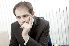 Depressed businessman thinking. Depressed worried businessman sitting at his desk, with his chin in his hand thinking and trying to make difficult decisions Stock Image