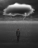 Depressed businessman walking with dark cloud of rain and lightning royalty free stock photography