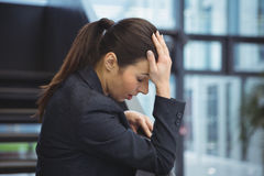 Depressed businesswoman with hand on her head. At office Stock Photos