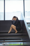Depressed businesswoman with hand on her head sitting on stairs. At office Stock Photos