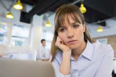 Depressed businesswoman in office behind her lapto Stock Image