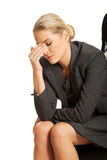 Depressed businesswoman sitting on armchair Royalty Free Stock Images