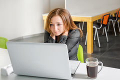 Depressed businesswoman sitting at computer. Tired and sleepy office worker looking at the laptop screen and needs help. Stock Photos