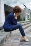 Depressed businesswoman sitting in the premises Stock Photography