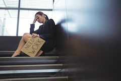 Depressed businesswoman sitting on stairs holding cardboard sheet with text need work Royalty Free Stock Photography