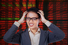 Depressed businesswoman with stock market background Stock Photos