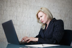 Depressed businesswoman typing on laptop Royalty Free Stock Images