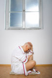 Depressed cancer patient sitting on hospital floor Royalty Free Stock Images