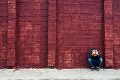 Depressed child and brick wall. Depressed abused upset crying child (boy, kid, teen) sitting near red brick wall Royalty Free Stock Images