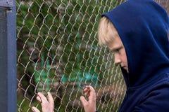 Depressed child. Depressed, frustrated boy (child, kid, teen) near metal mesh, close up portrait, children problems concept Stock Photo
