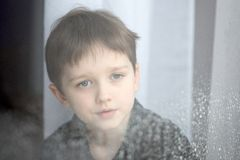 Depressed child looking out the window. Stock Photo