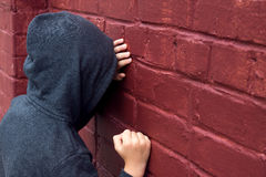 Depressed child. Worried depressed sad teen boy (child) crying near brick wall Royalty Free Stock Photography