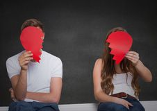 Depressed couple holding broken heart against grey background