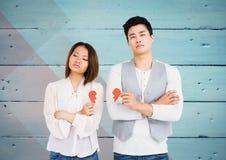 Depressed couple holding broken heart Stock Images
