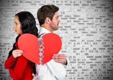 Depressed couple holding broken heart. Depressed couple standing back to back holding broken heart Royalty Free Stock Photography