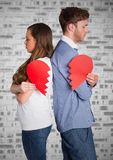 Depressed couple holding broken heart. Depressed couple standing back to back holding broken heart Stock Images